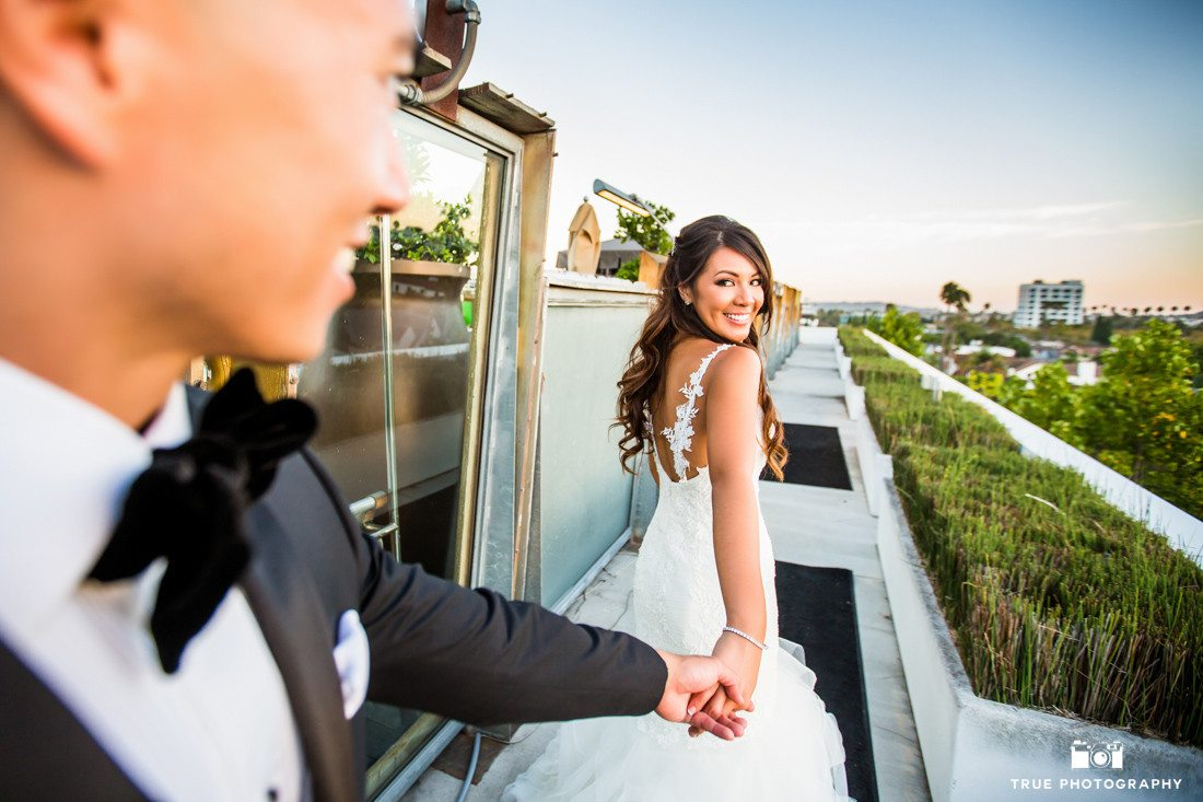 Photograph of smiling bride holding hands with groom at the SLS Hotel in Beverly Hills California