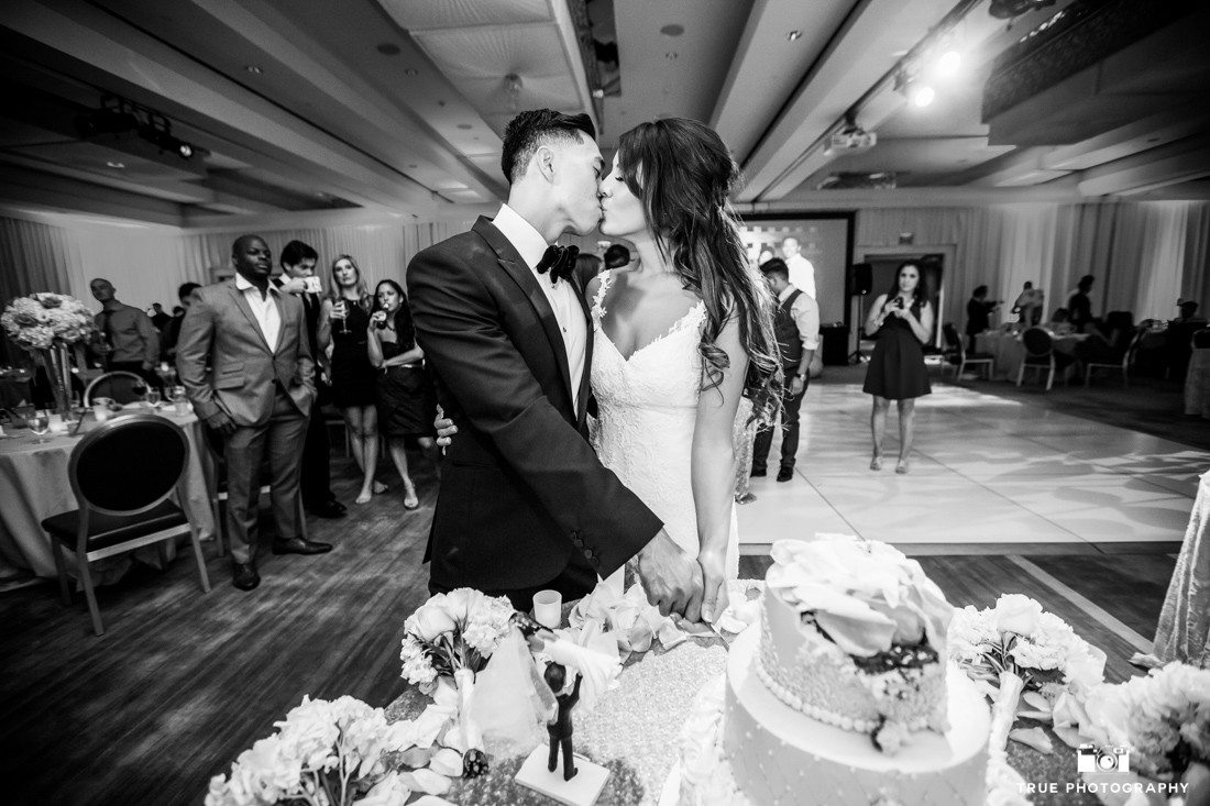 Kissing bride and groom cutting their wedding cake at the SLS Hotel in Beverly Hills.