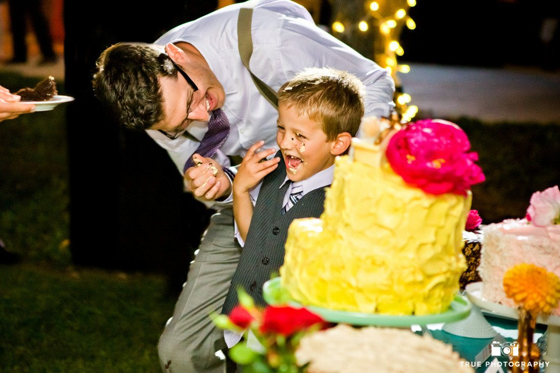 Groom smashes cake into boys face during wedding reception