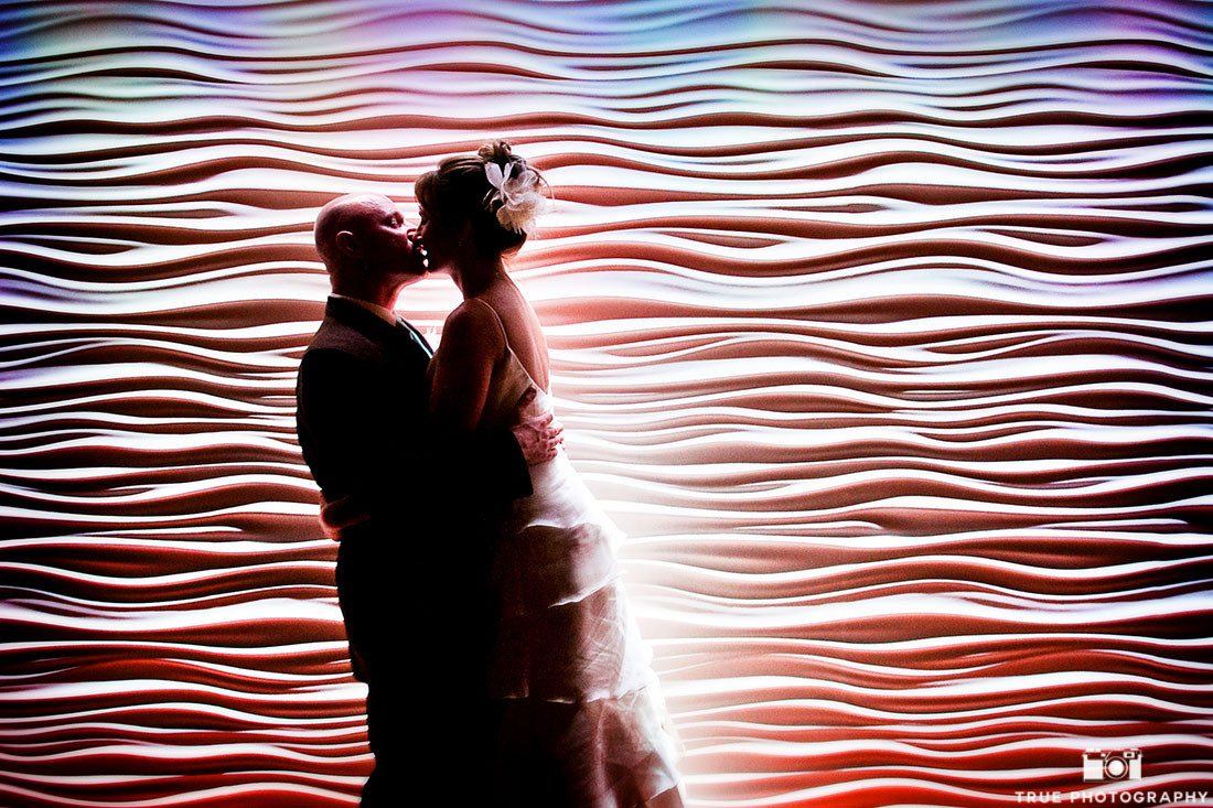 Bride and Groom pose and kiss in front of modern romantic backdrop with dramatic lighting
