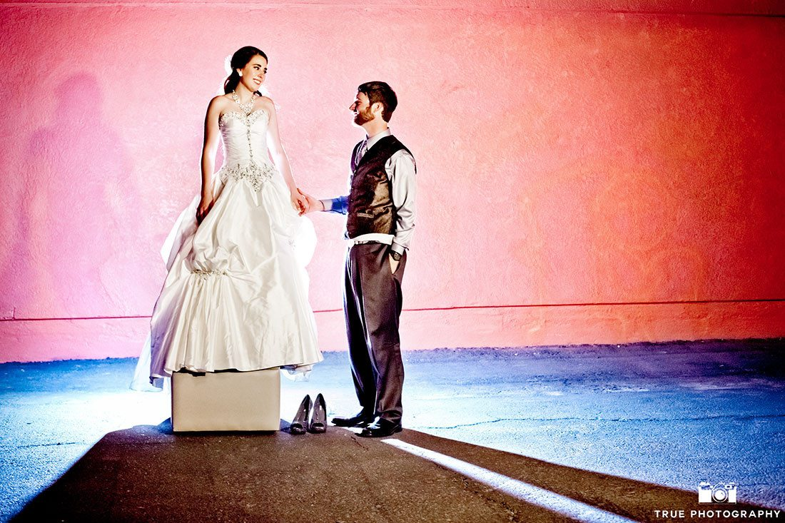 Bride and Groom pose in modern location with creative blue and pink backlight