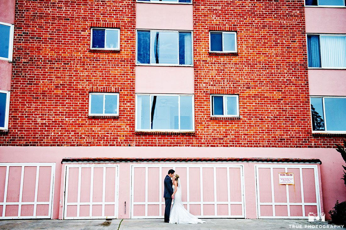Modern Bride and Groom kissing in front of Urban Blue and Pink Backdrop