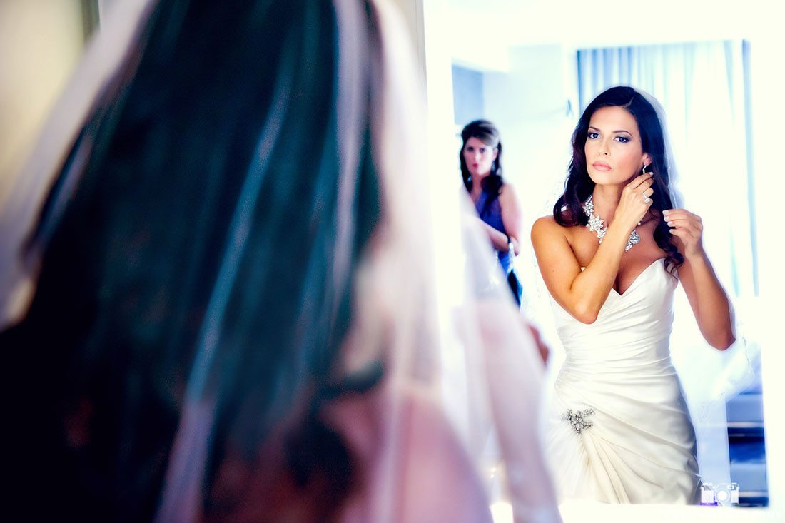 Modern Bride putting on jewelry and looking in mirror preparing for wedding day