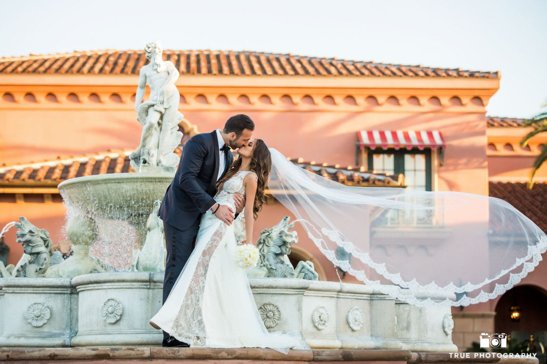 Couple kiss by fountain at Fairmont Grand Del Mar