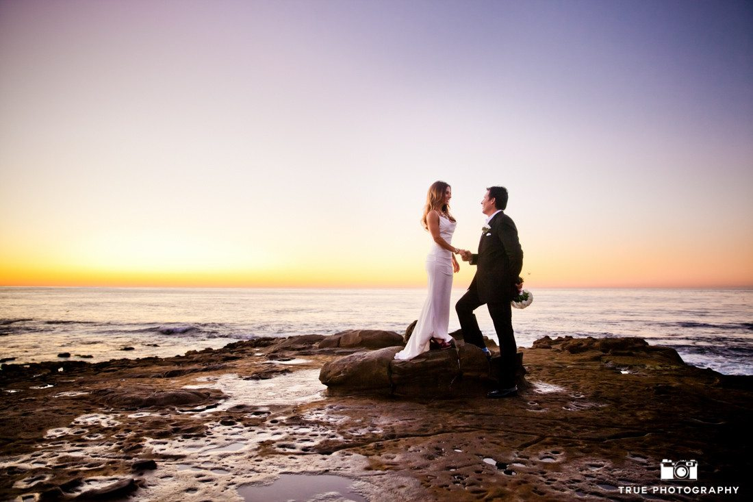 Couple pose in front of sunset sky at La Jolla Cove