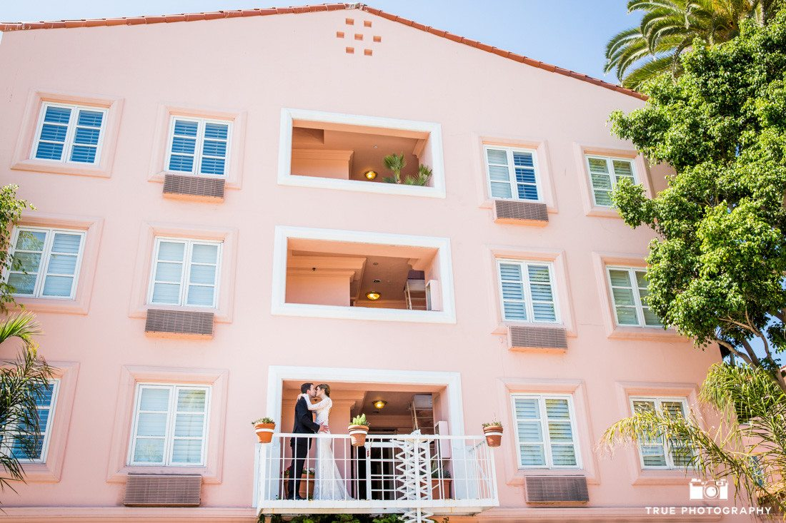 Bride and Groom lean in for kiss out on balcony at La Valencia