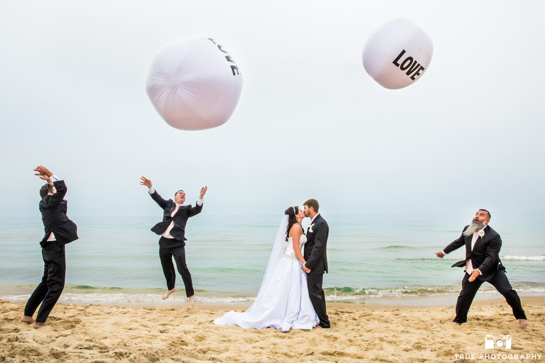 Bride and Groom have fun with balloon props at Silver Beach