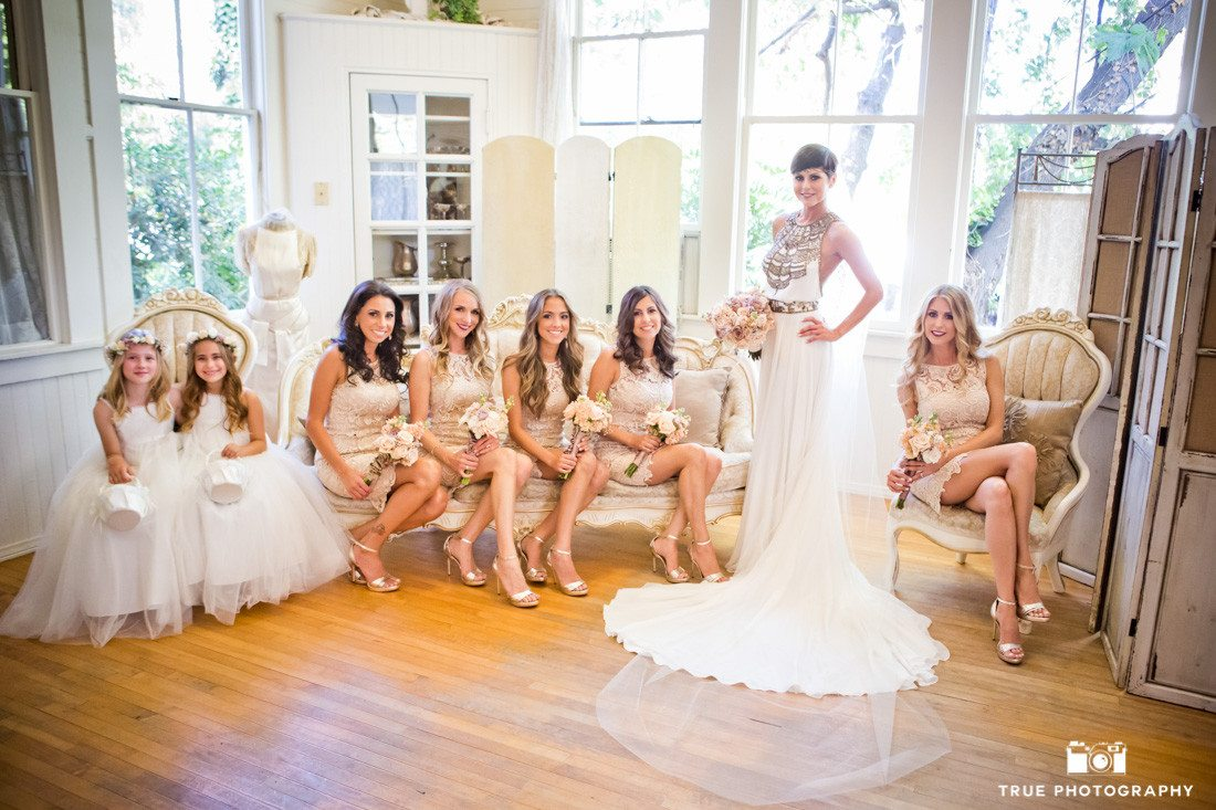 Bridesmaids look at Bride in dress during pre-ceremony