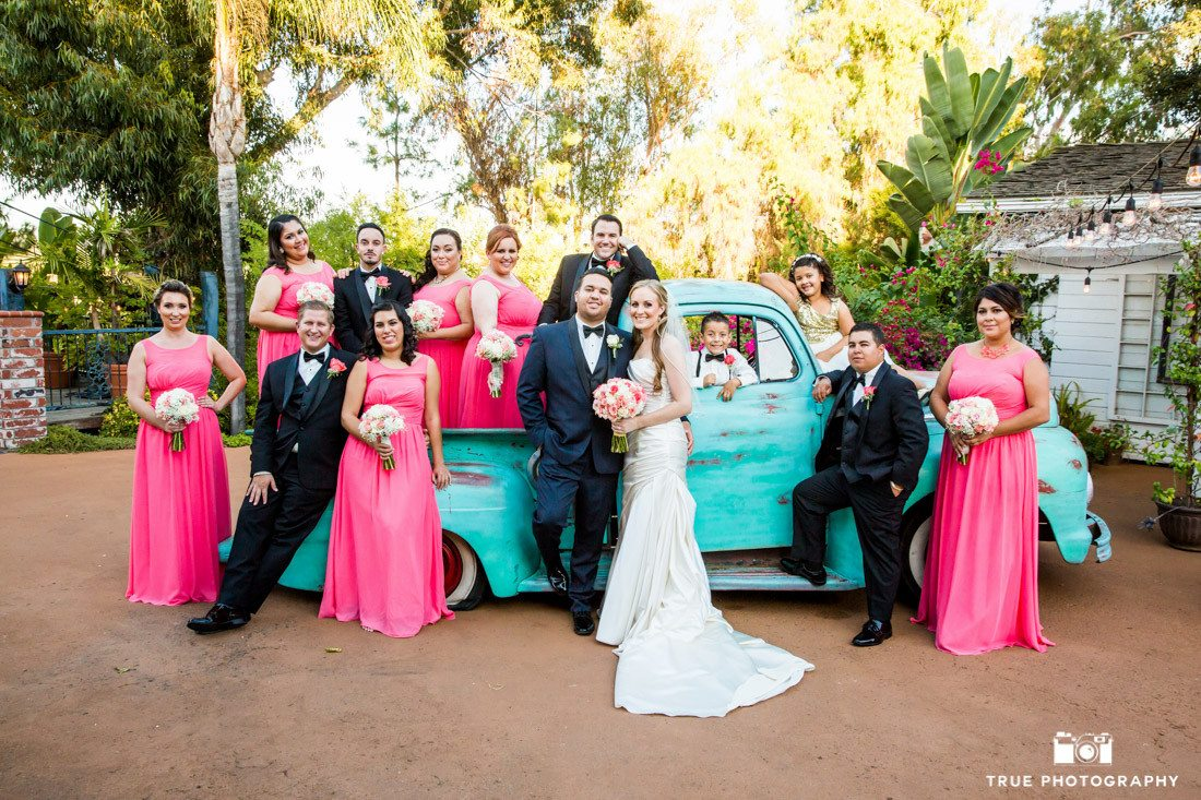 Colorful bridal party poses with vintage truck