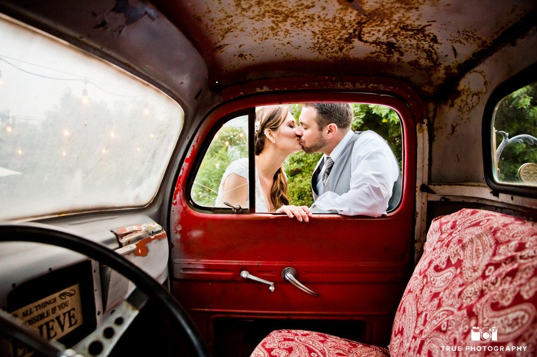 Bride and Groom lean in for kiss through truck window