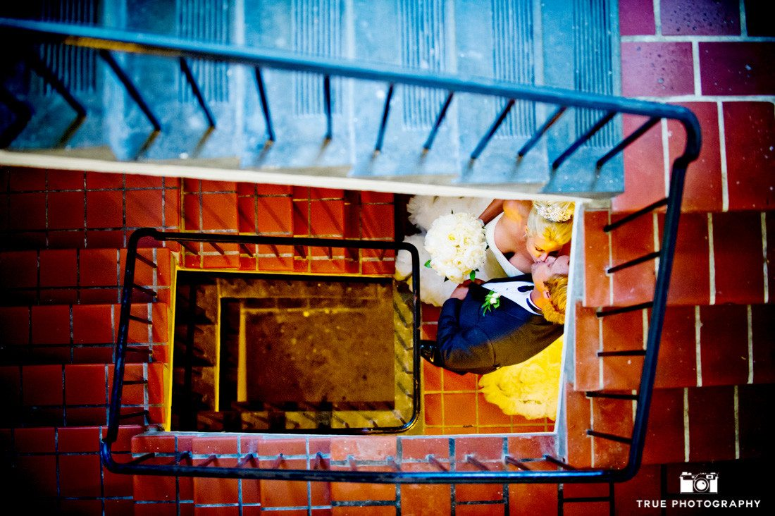 Bride and Groom lean in for an artistic photo of them kissing down stairwell