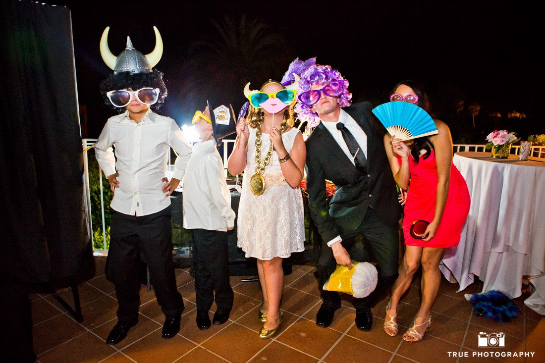 Guests at wedding reception have fun with photobooth