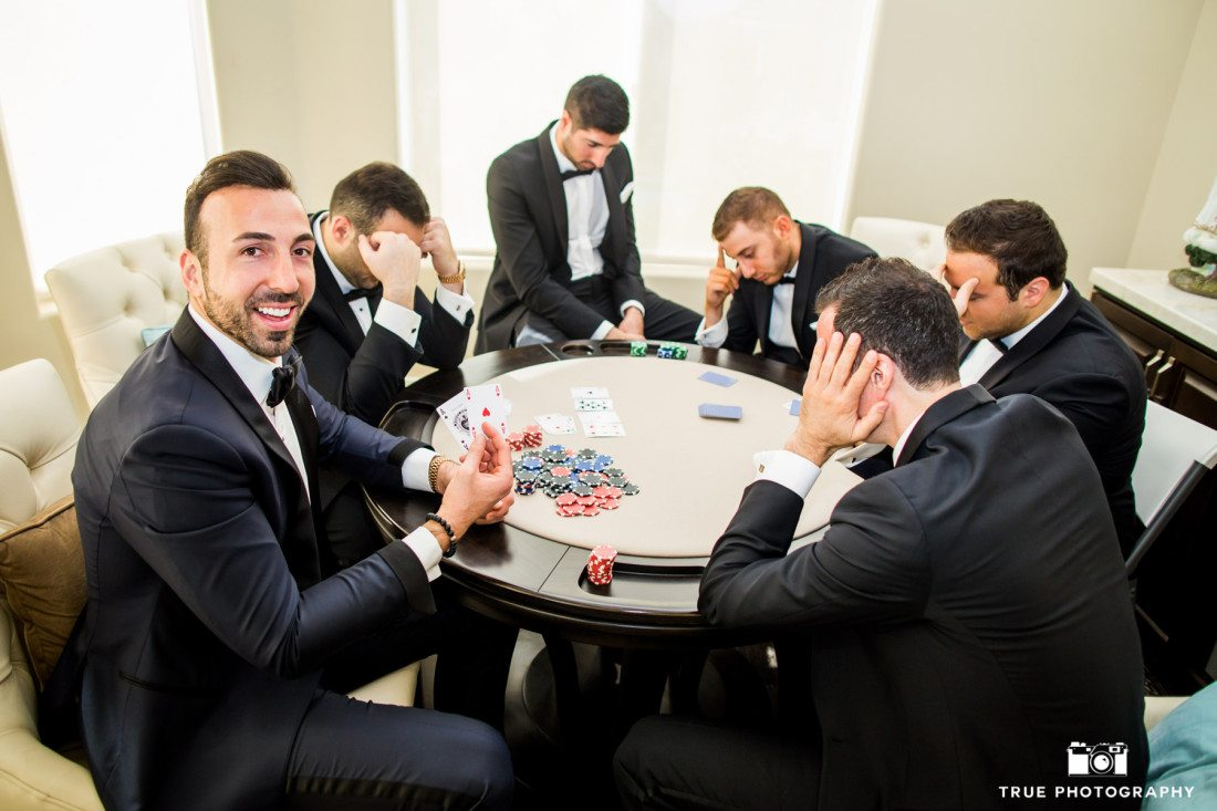 Groomsmen pose for fun photo playing poker before ceremony