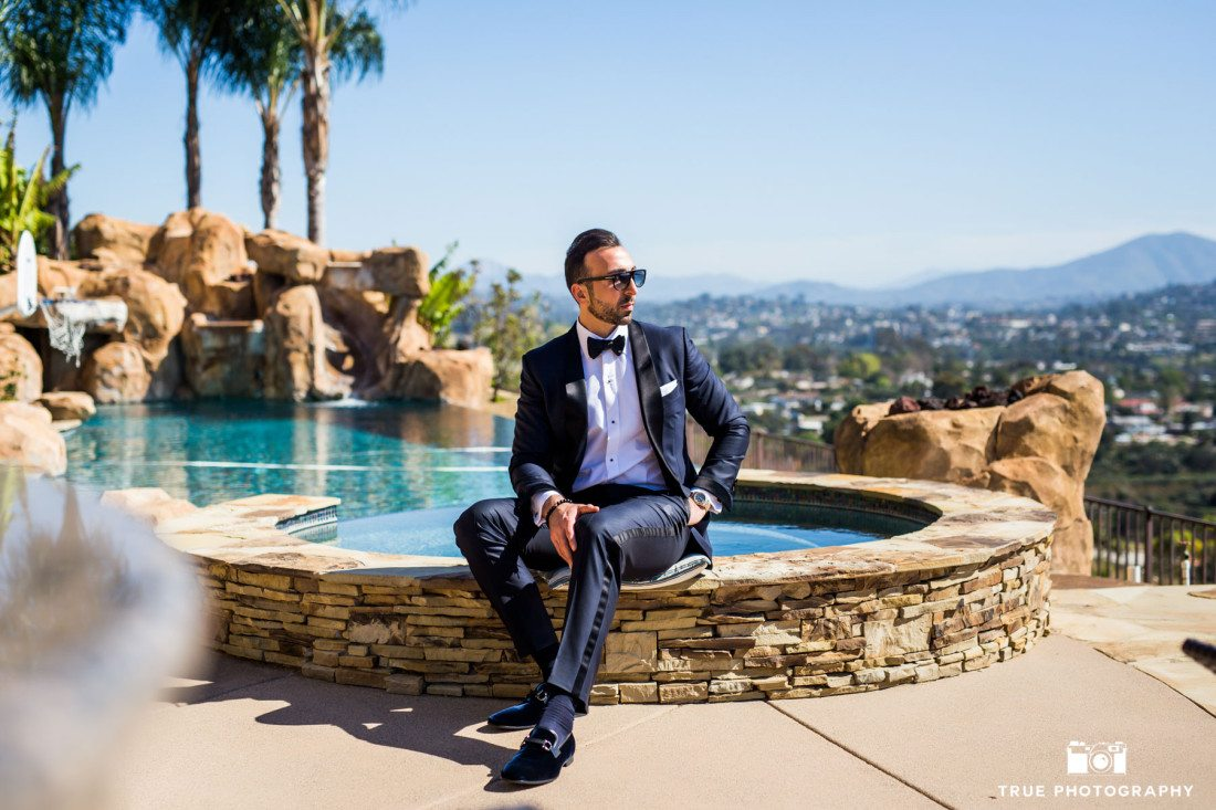 Modern Groom sits by Pool