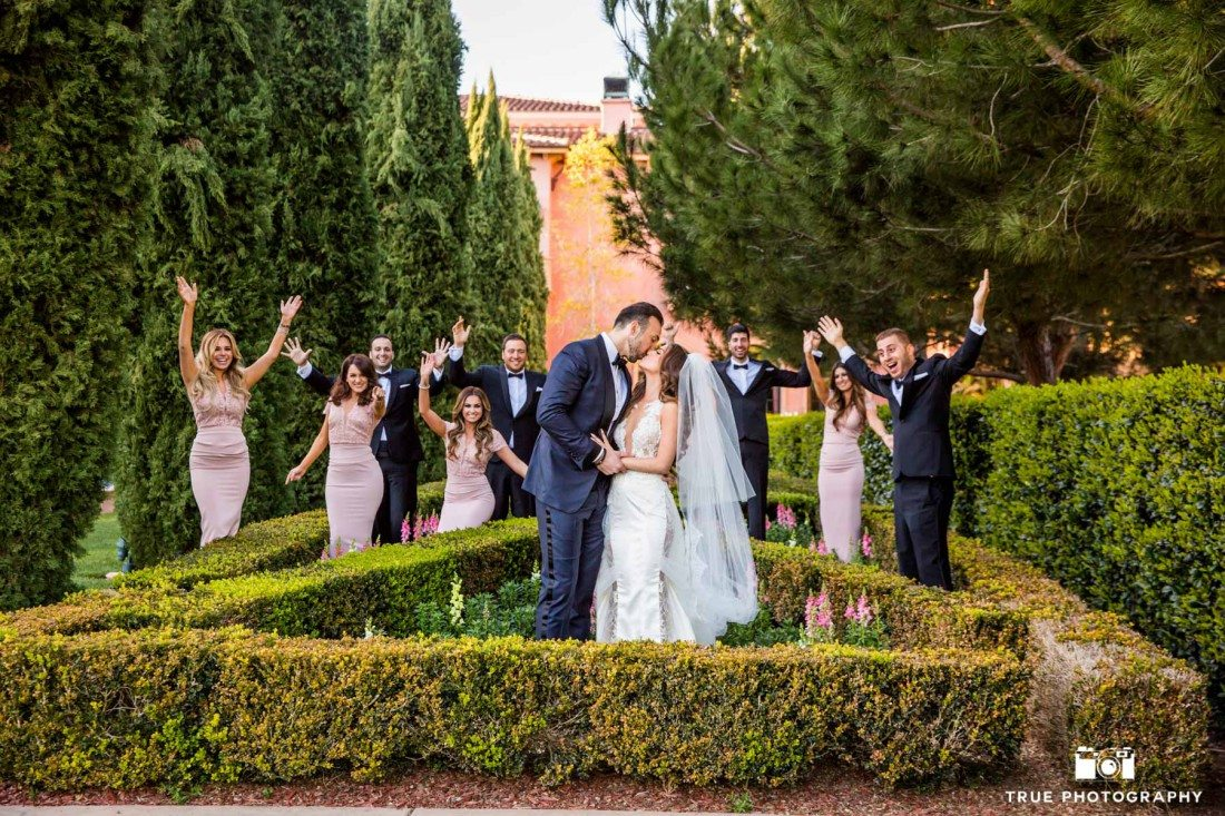 Couple share kiss at Grand Del Mar with Bridal Party celebrating