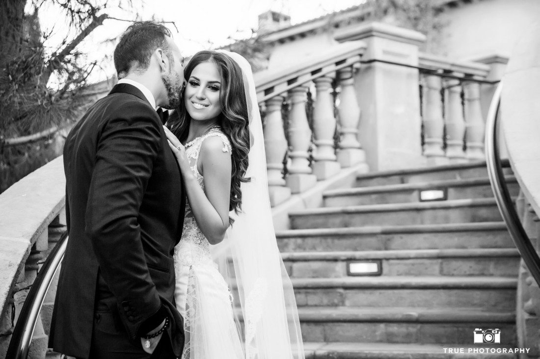 Intimate, black-and-white photo of bride and groom kissing on balcony at Grand Del Mar