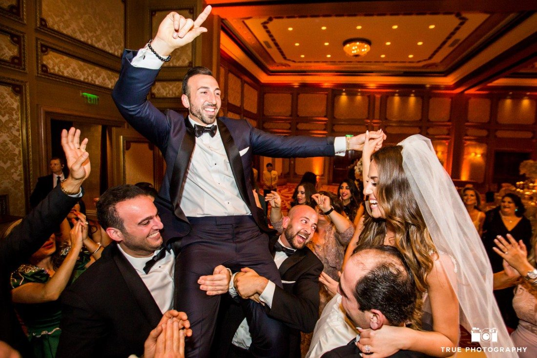 Groomsmen lift groom off ground during reception at Grand Del Mar
