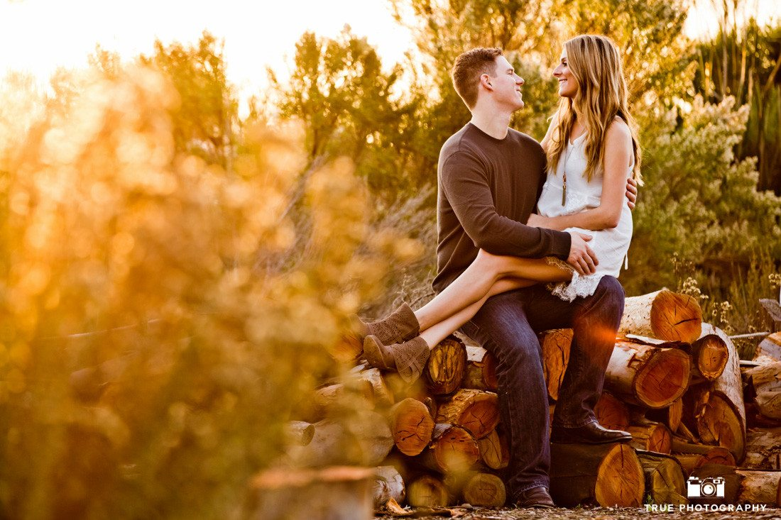 Rustic engagement photo of couple sitting on logs at dusk