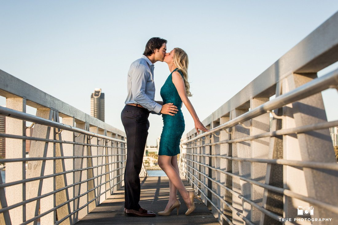 Engagement photo of couple kissing on boat dock is San Diego, California