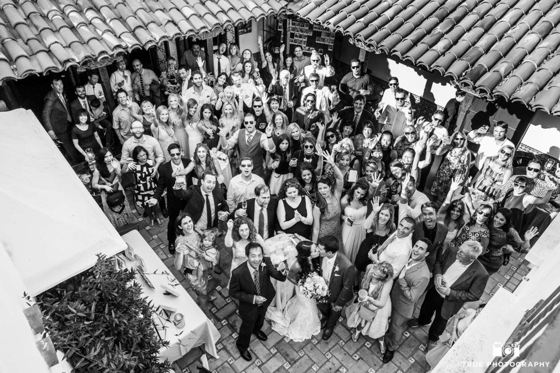 Big Group Wedding Photo of couple kissing at the Darlington House in La Jolla, California