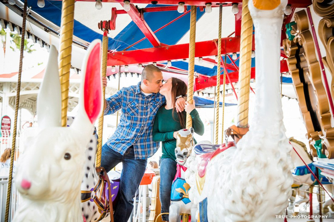 Engagement photo of couple on Carousel at Belmont Park San Diego, Califronia
