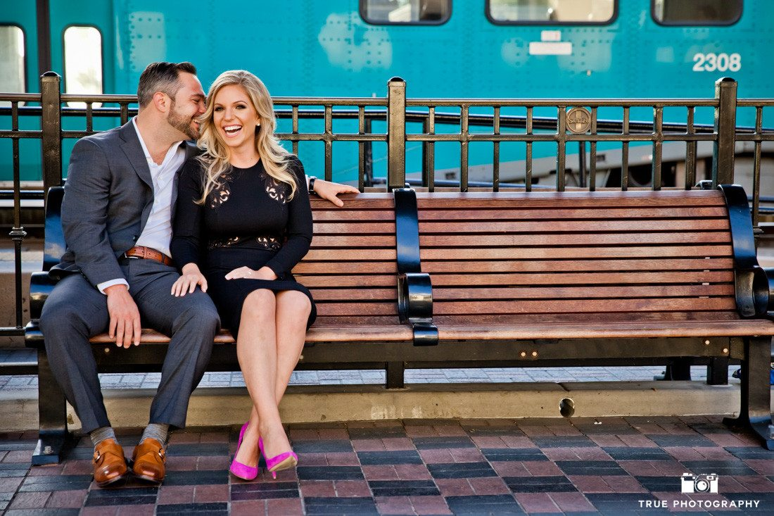 Fun candid engagement photo at a train station.