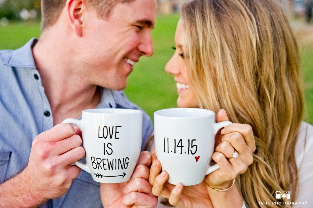 Save the Date engagement photograph of couple holding coffee mugs.