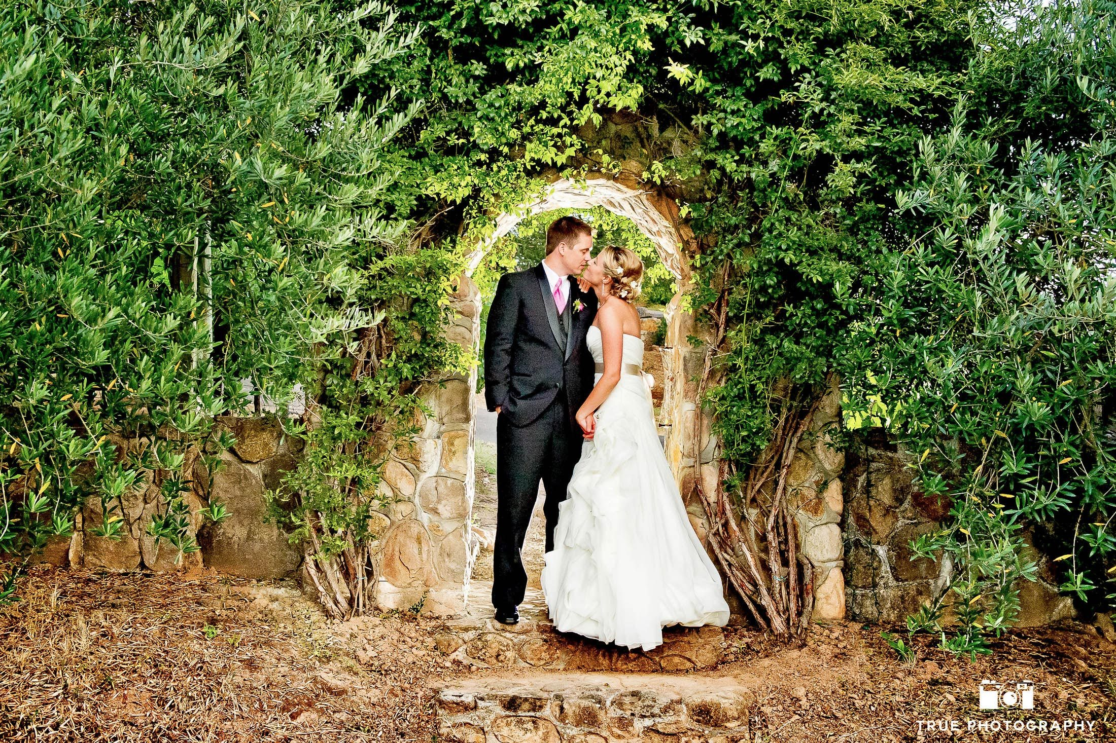 Bride and Groom kissing under natural archway
