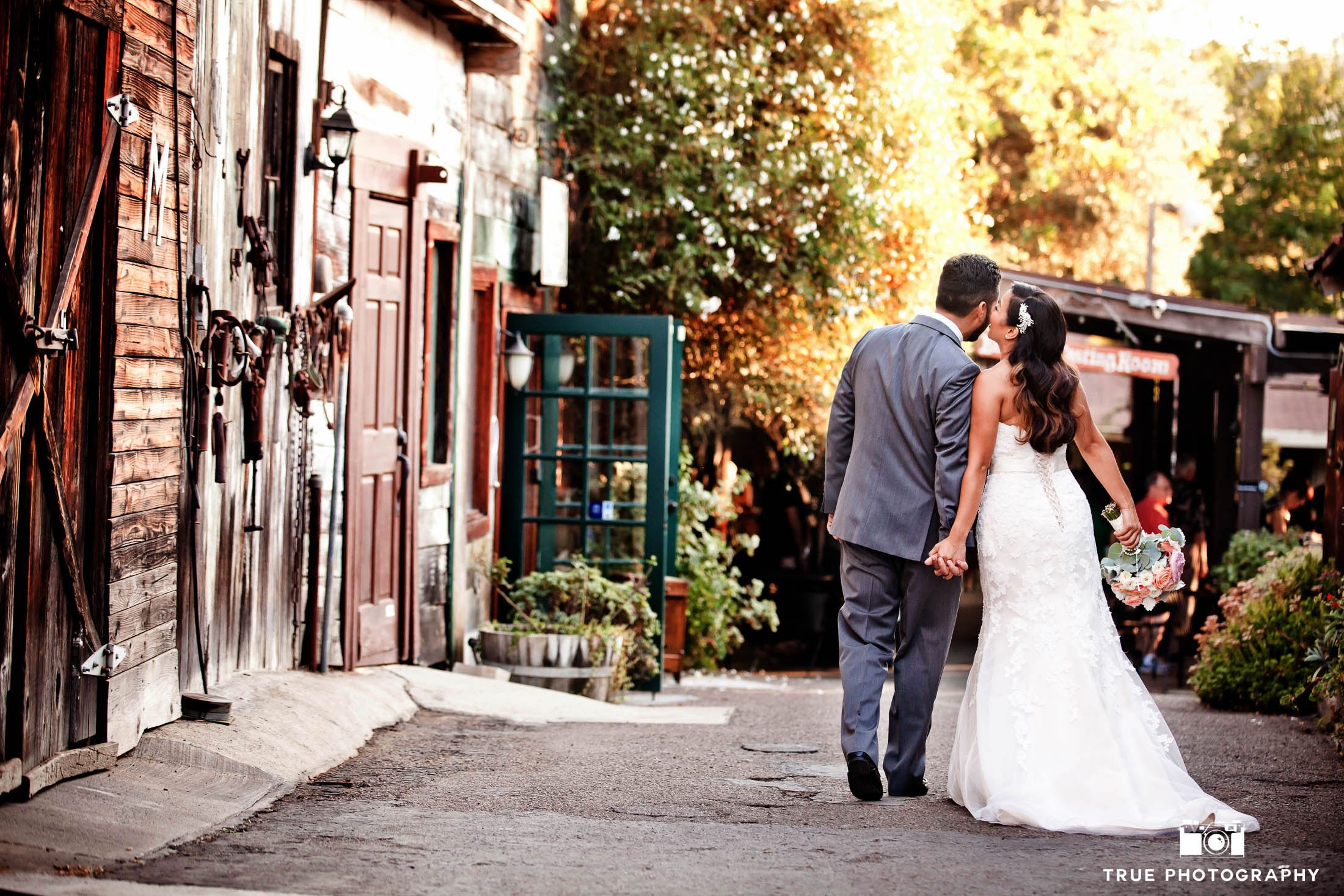 Couple holding hands and kissing with rustic background