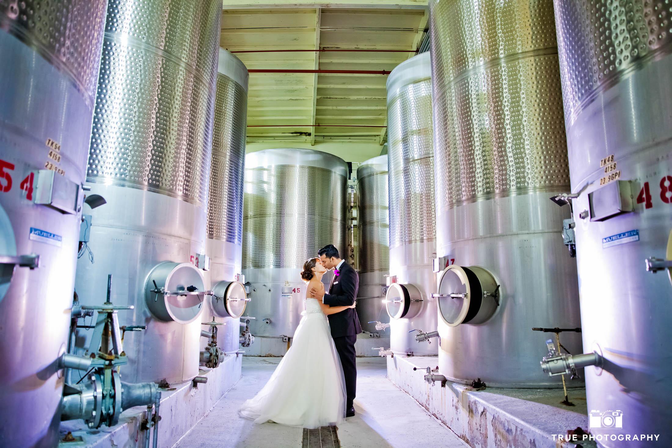 Couple kiss between distillery tanks at vineyard