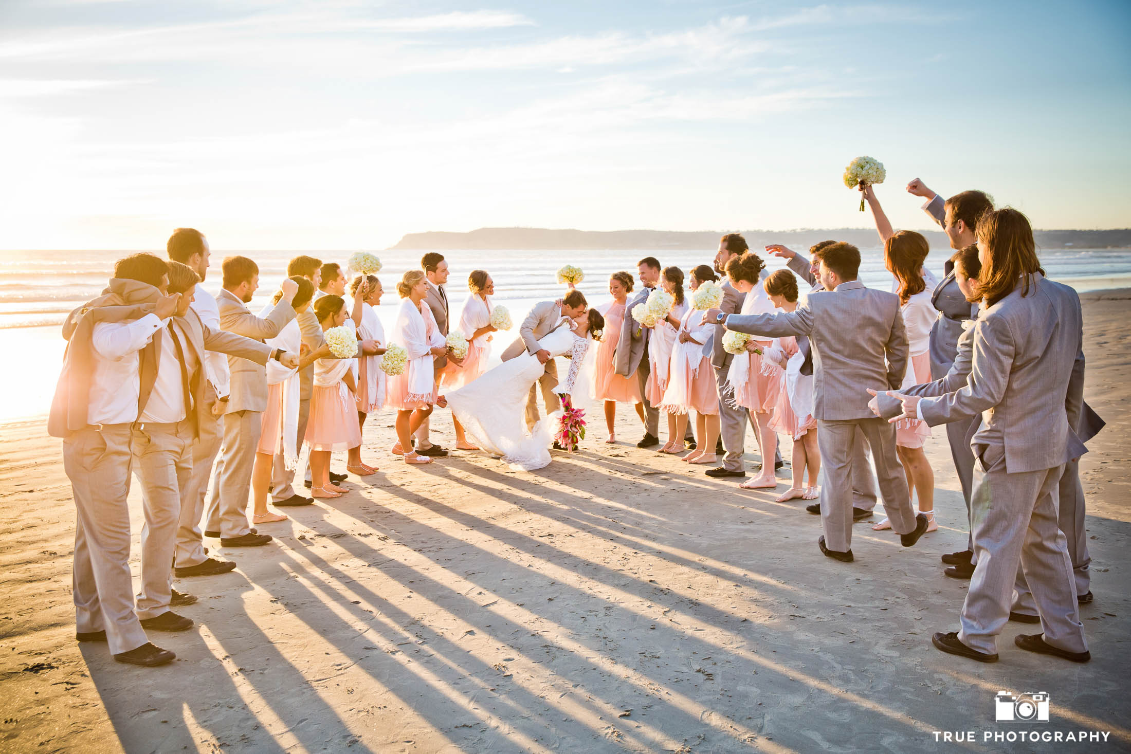 Bridal party cheers while wedding couple dip and kiss on Coronado beach