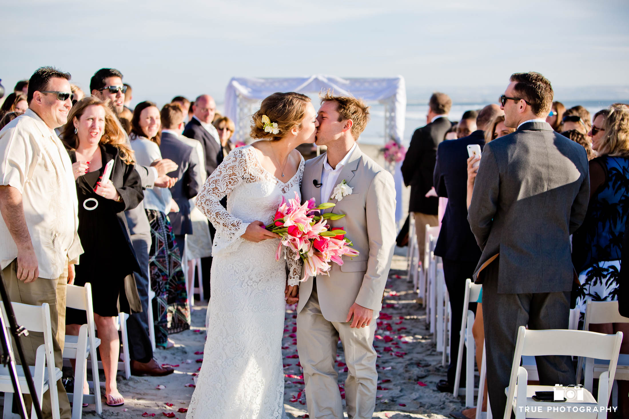 Coronado, California wedding couple kissing at beach wedding ceremony
