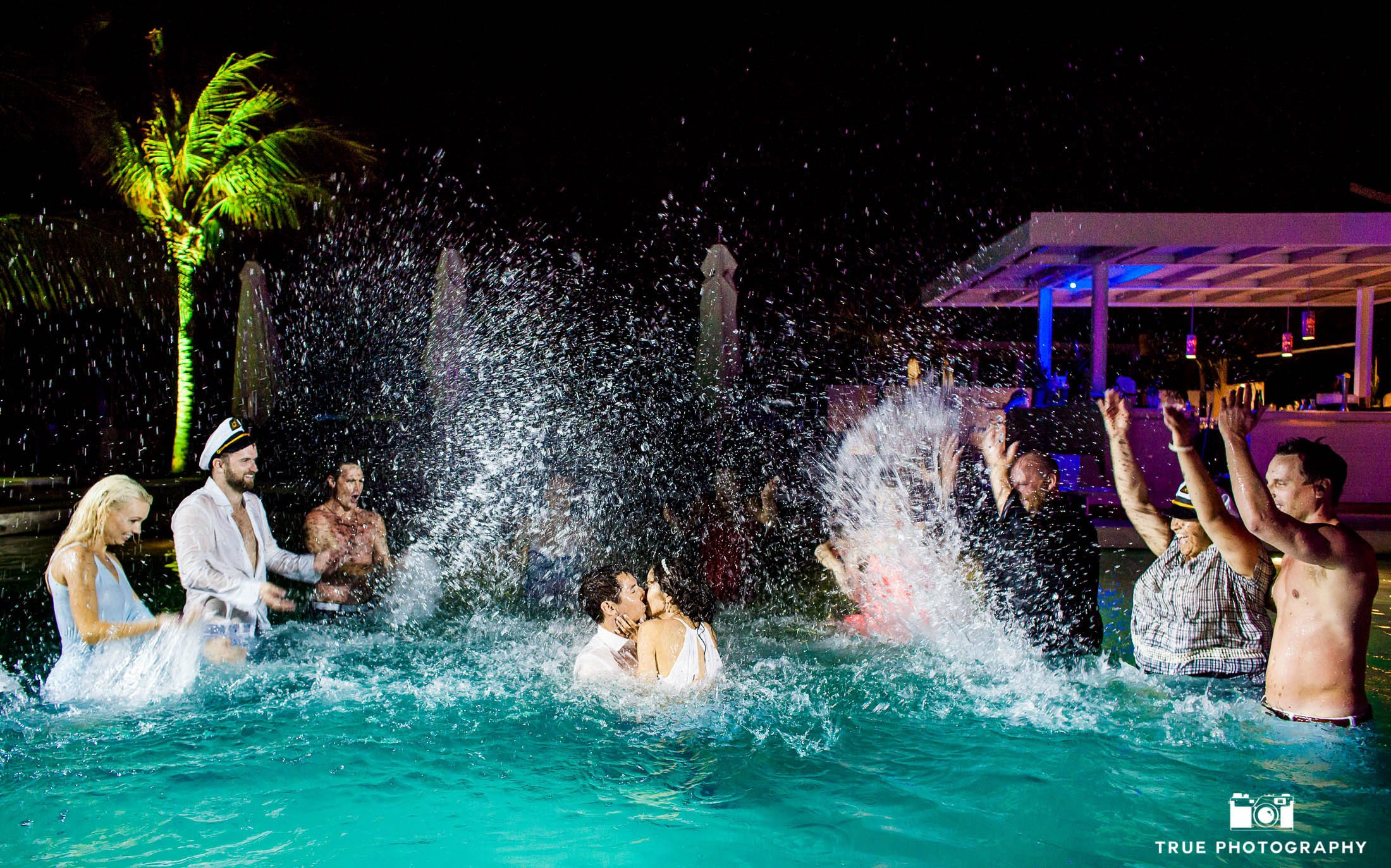 Bride and groom jump in pool for a kiss in Playa del Carmen.