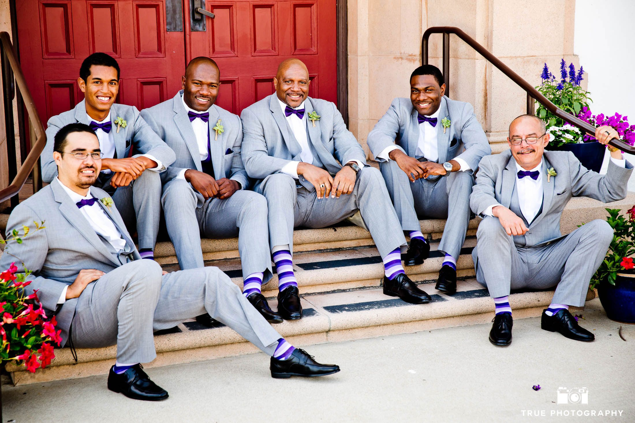 Groomsmen sit casually on steps