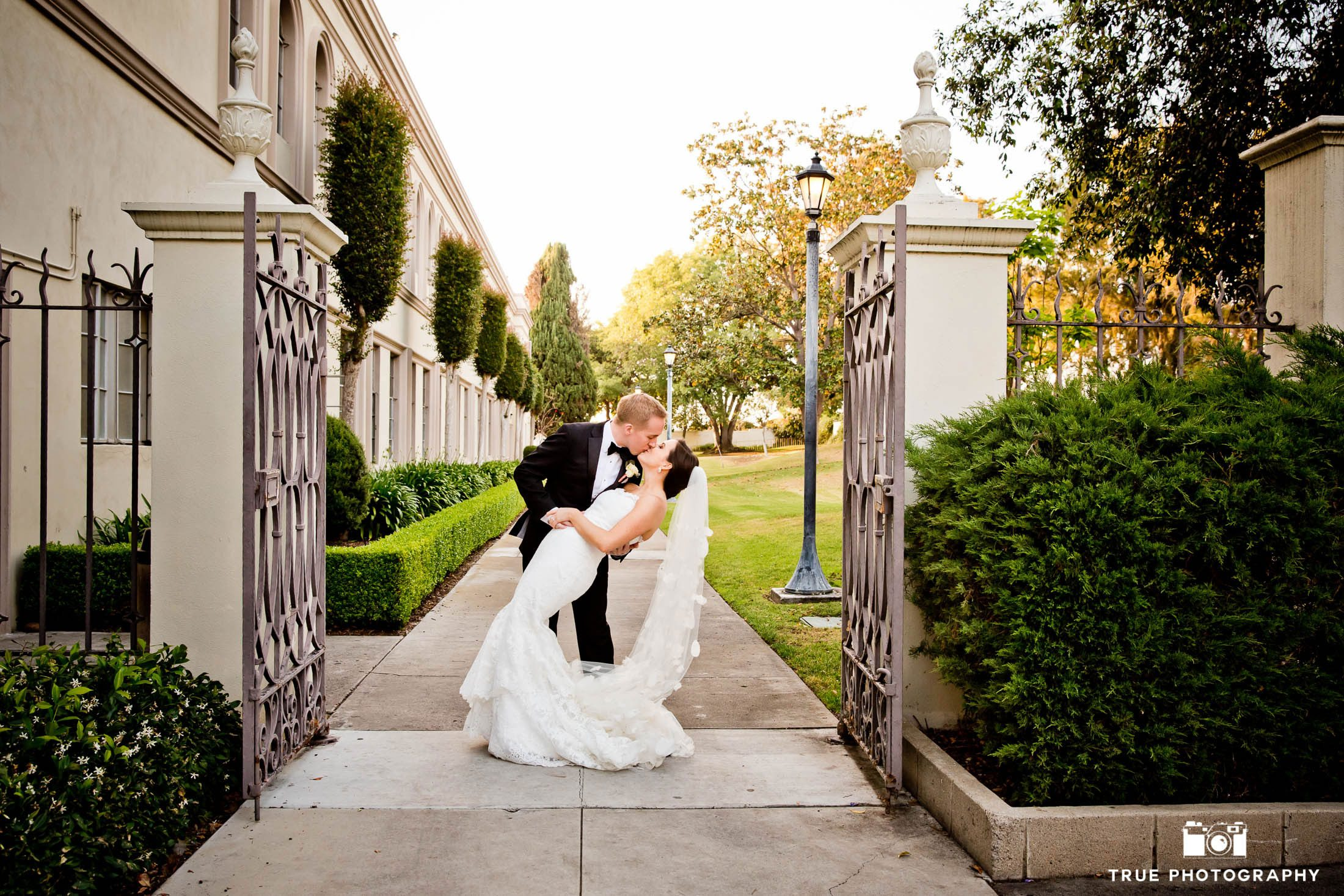 A groom tilts his new bride back for a fashionable kiss near the gates of Founders chapel.
