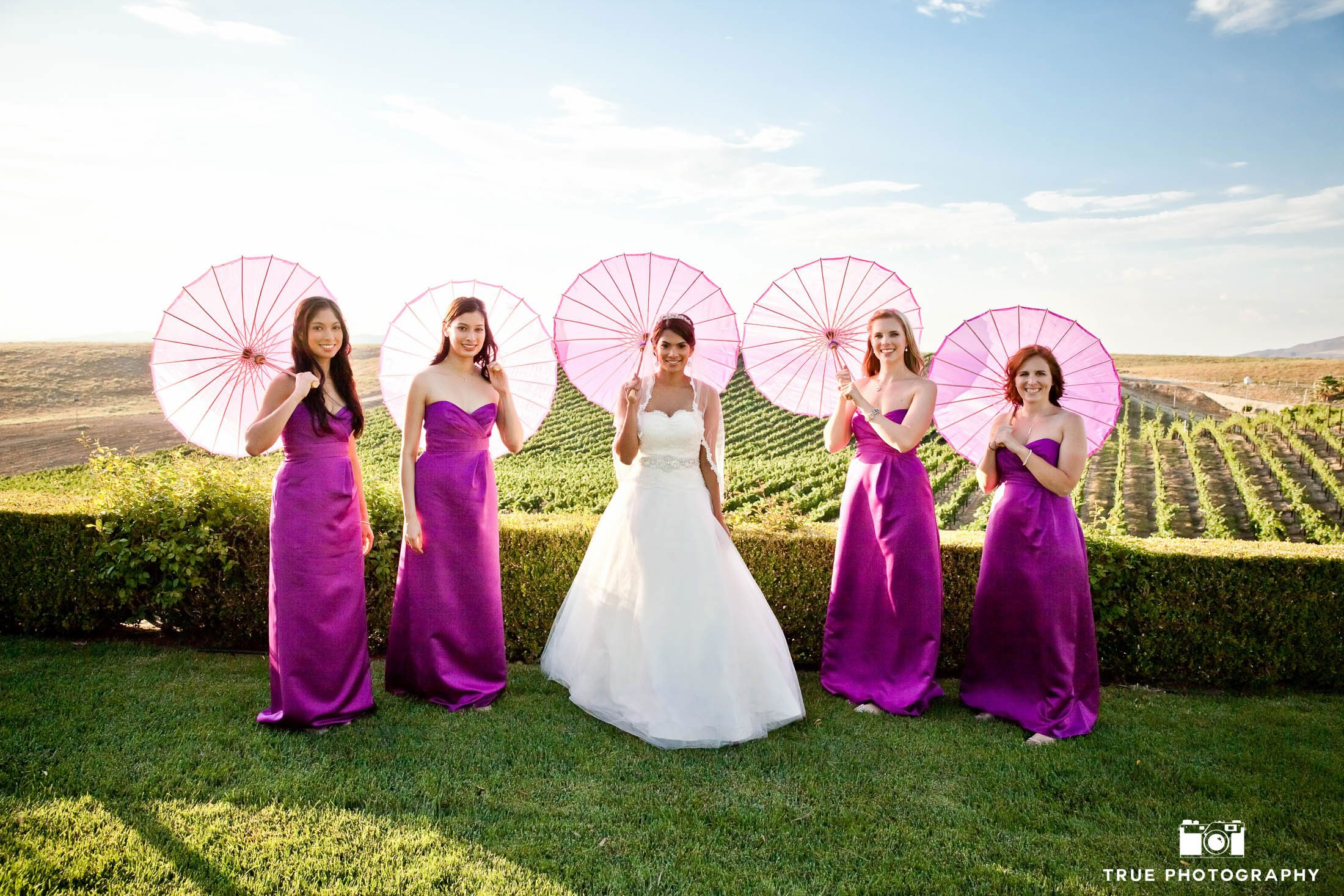 Bridesmaid with parasol umbrellas in vineyard