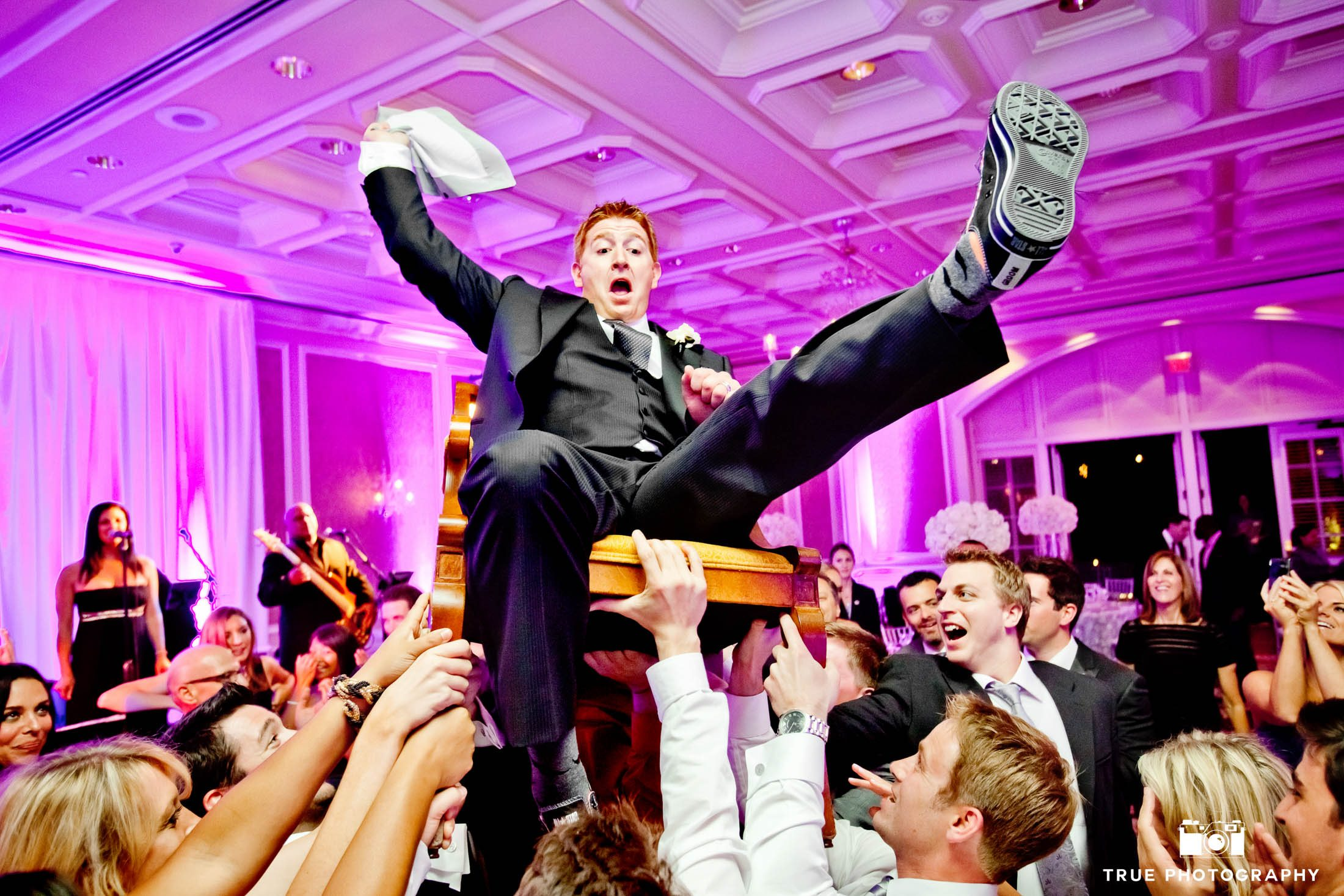 Groom is lifted in air by guests for hora dance