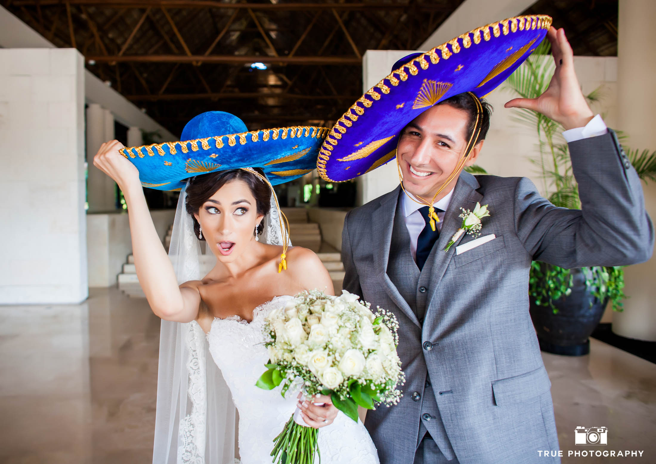 Newlyweds wearing blue sombreros in Mexico