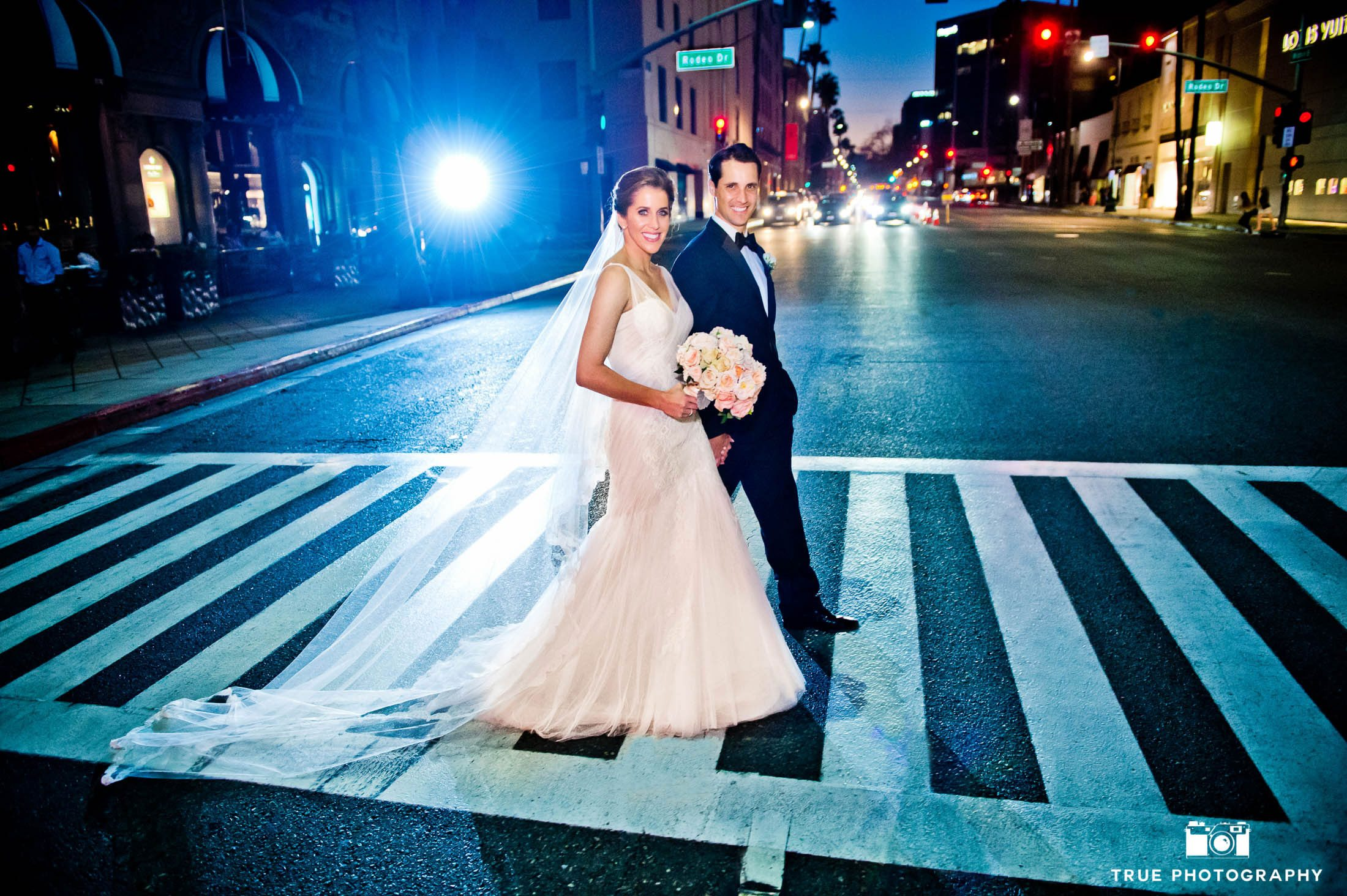 Bride and groom walking in San Diego during night photo