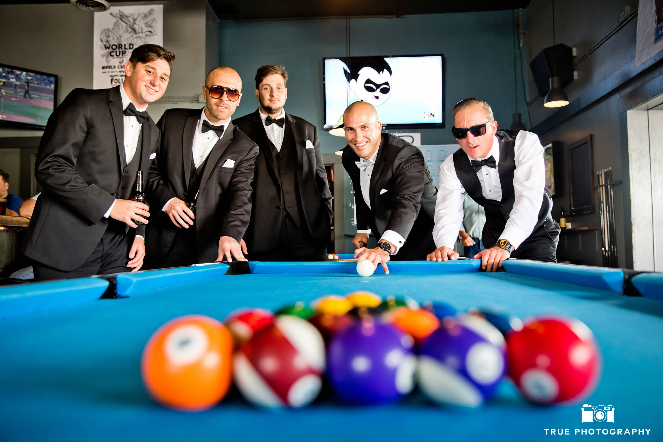 Groomsmen having fun playing pool before wedding ceremony