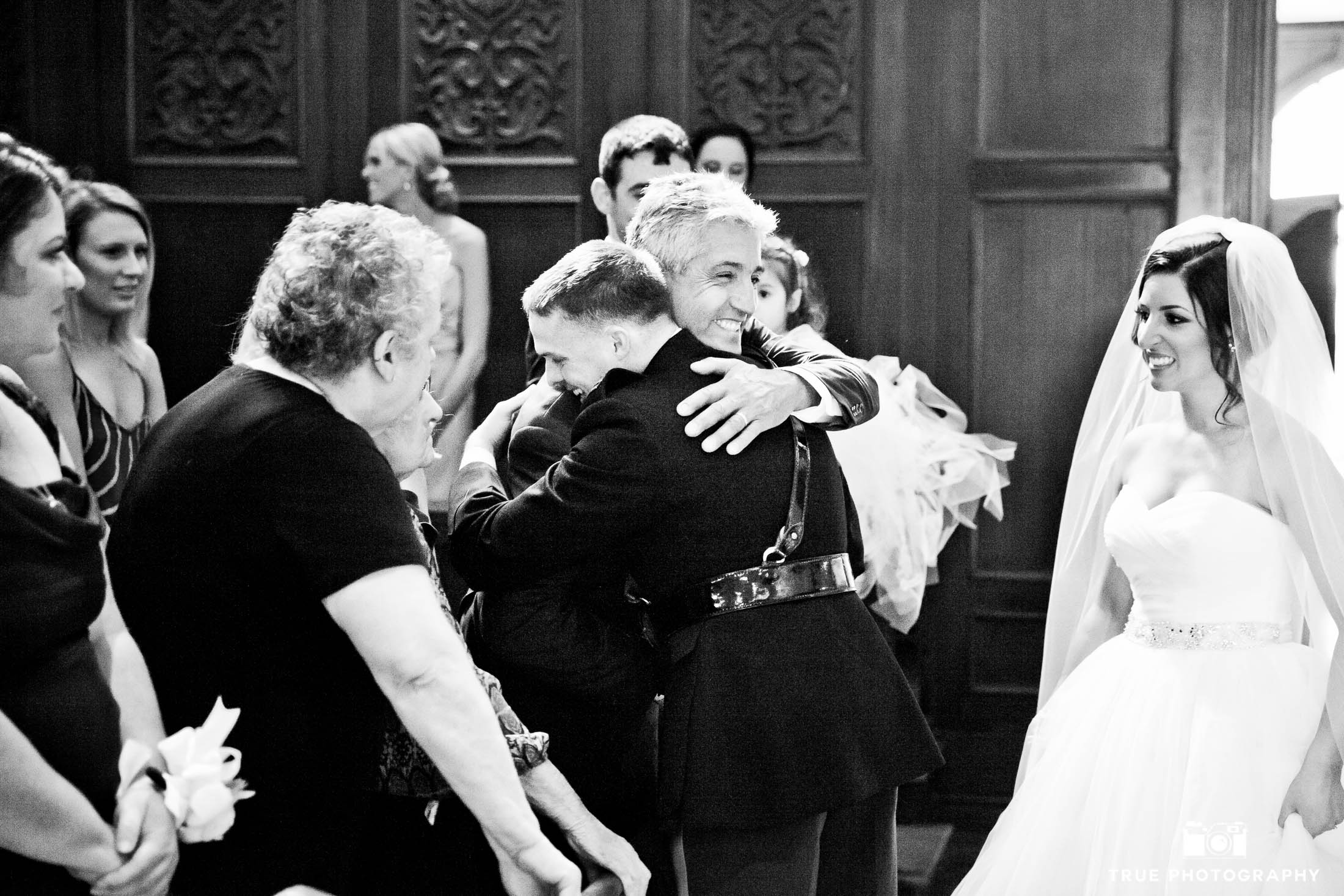 The Father of the bride hugs the groom during a ceremony at Founders Chapel at USD