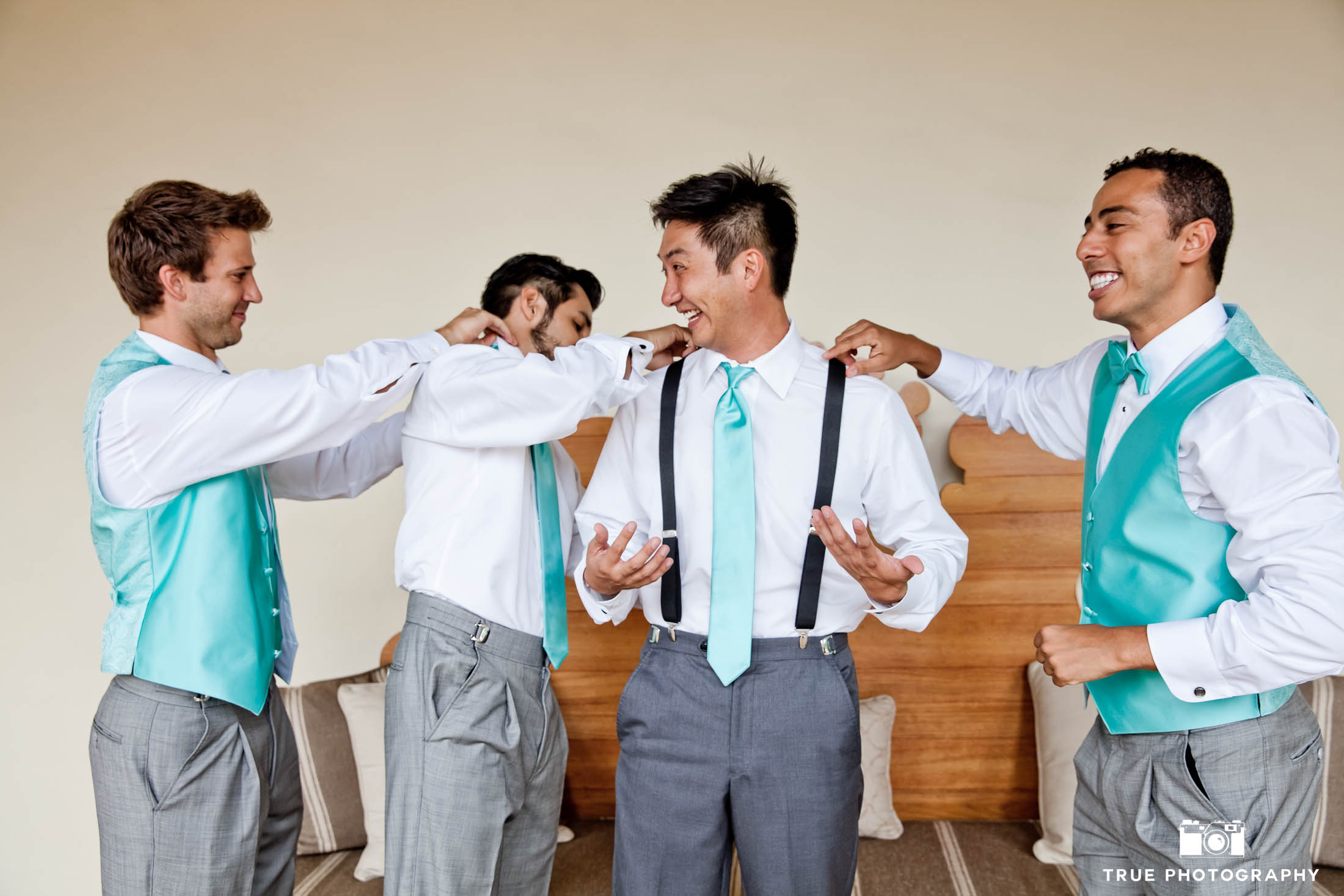 Groomsmen help the groom with his outfit