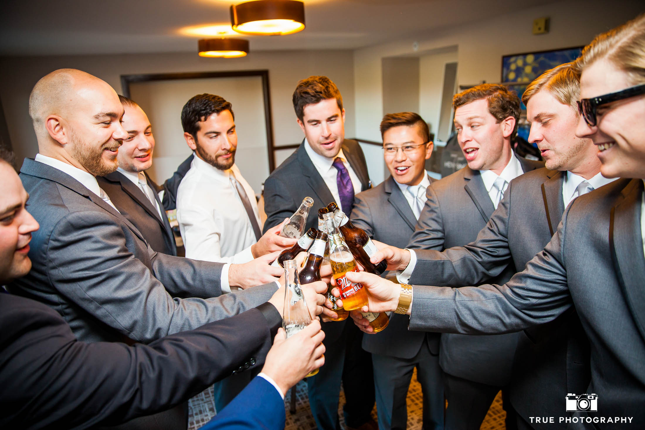 Groomsmen relax and cheers for a beer