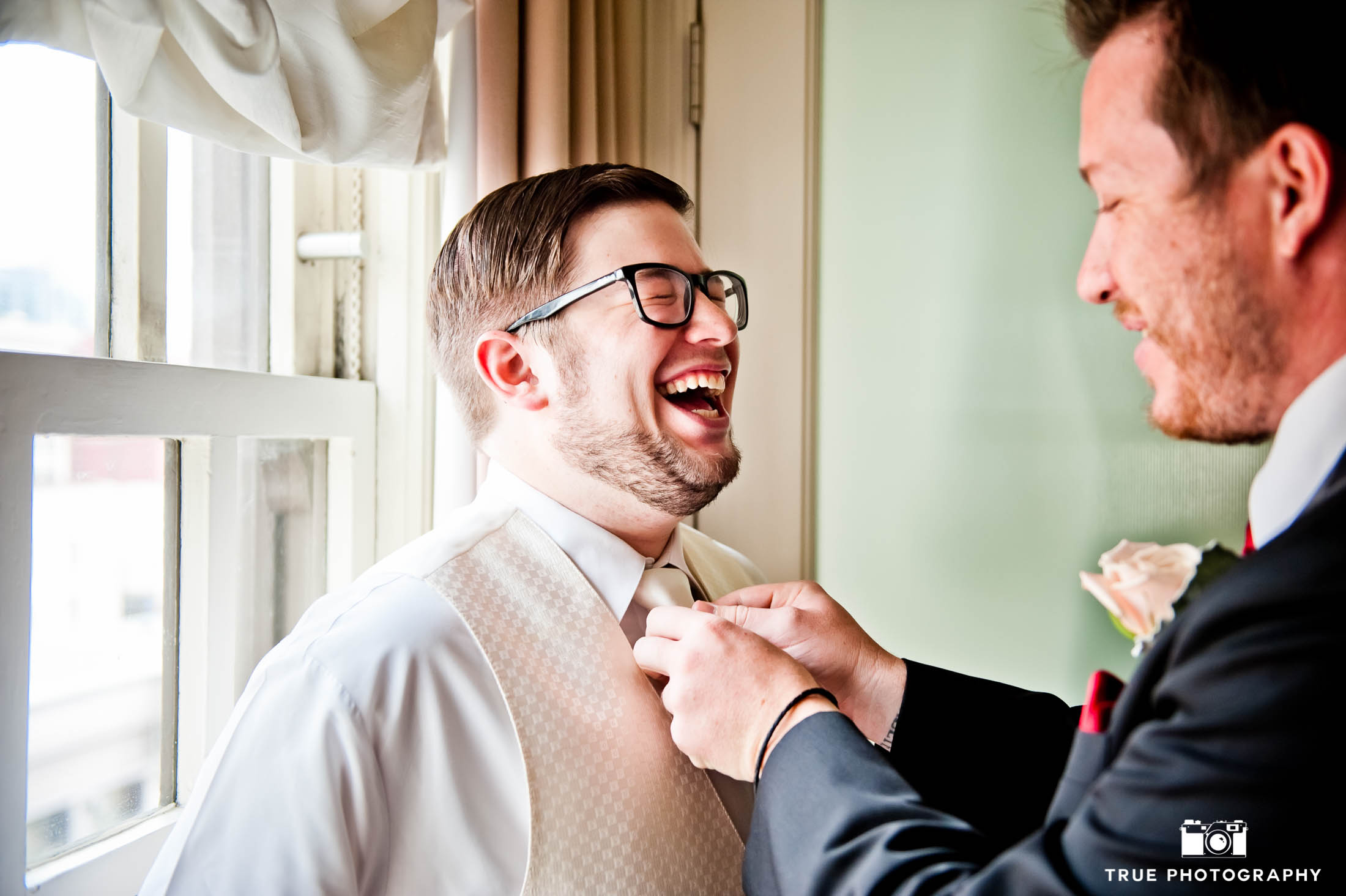 Groom laughing as he puts on tie