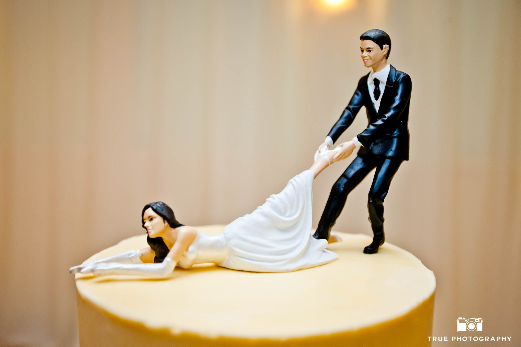 Funny cake topper with groom pulling bride