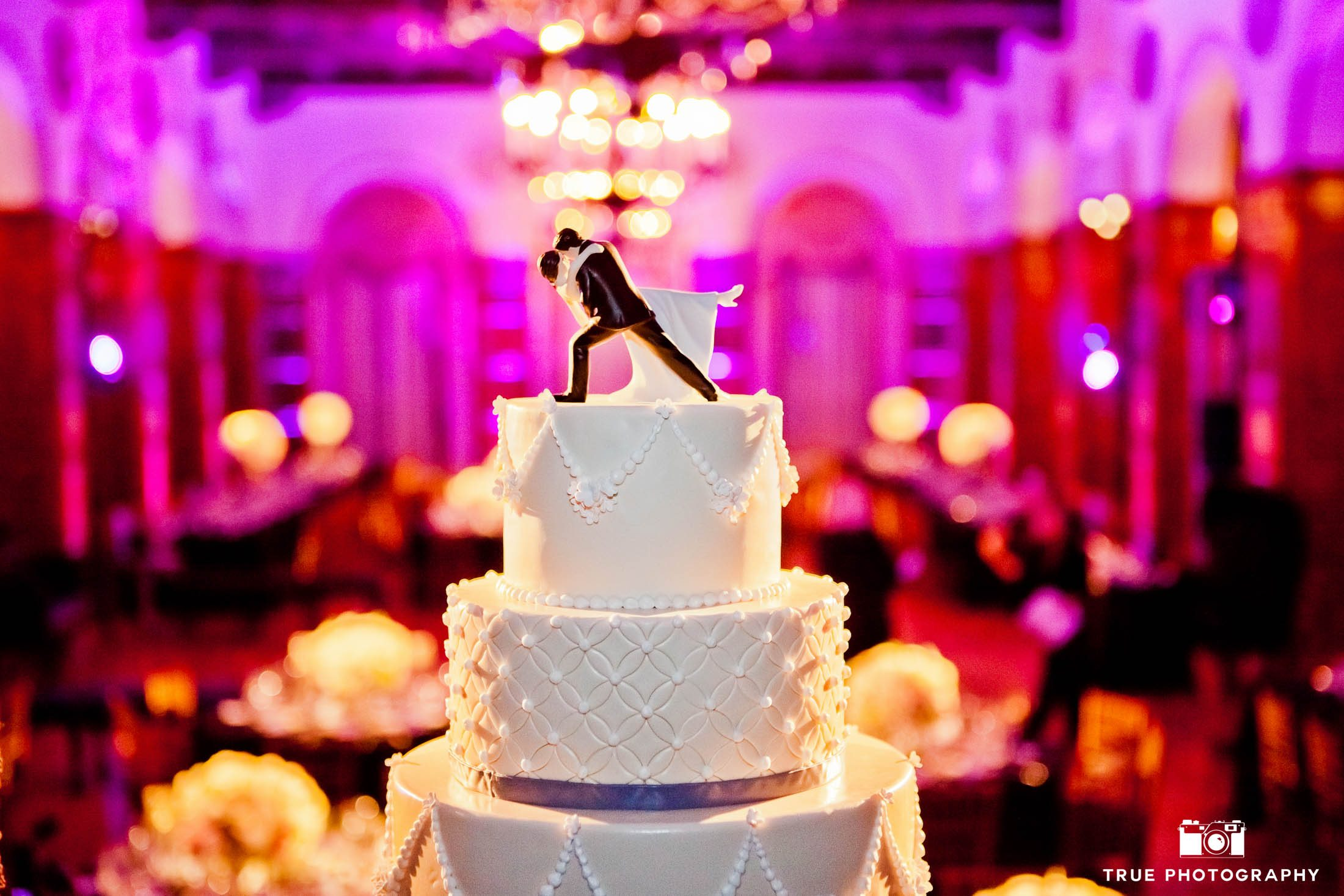 Classic wedding cake with cake topper of bride and groom kissing