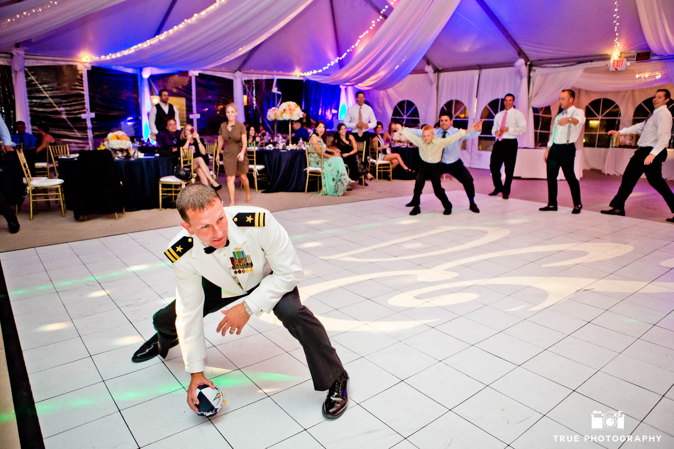 Groom prepares to throw garter during wedding reception
