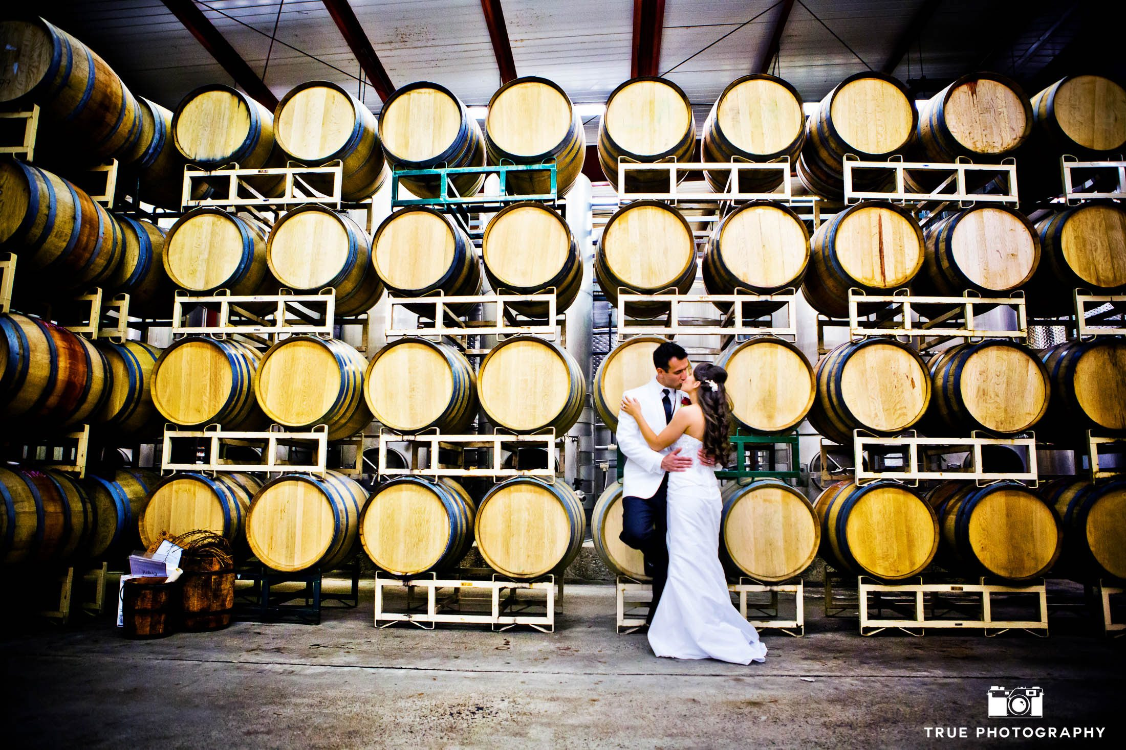 Couple Kiss in front of wine barrels