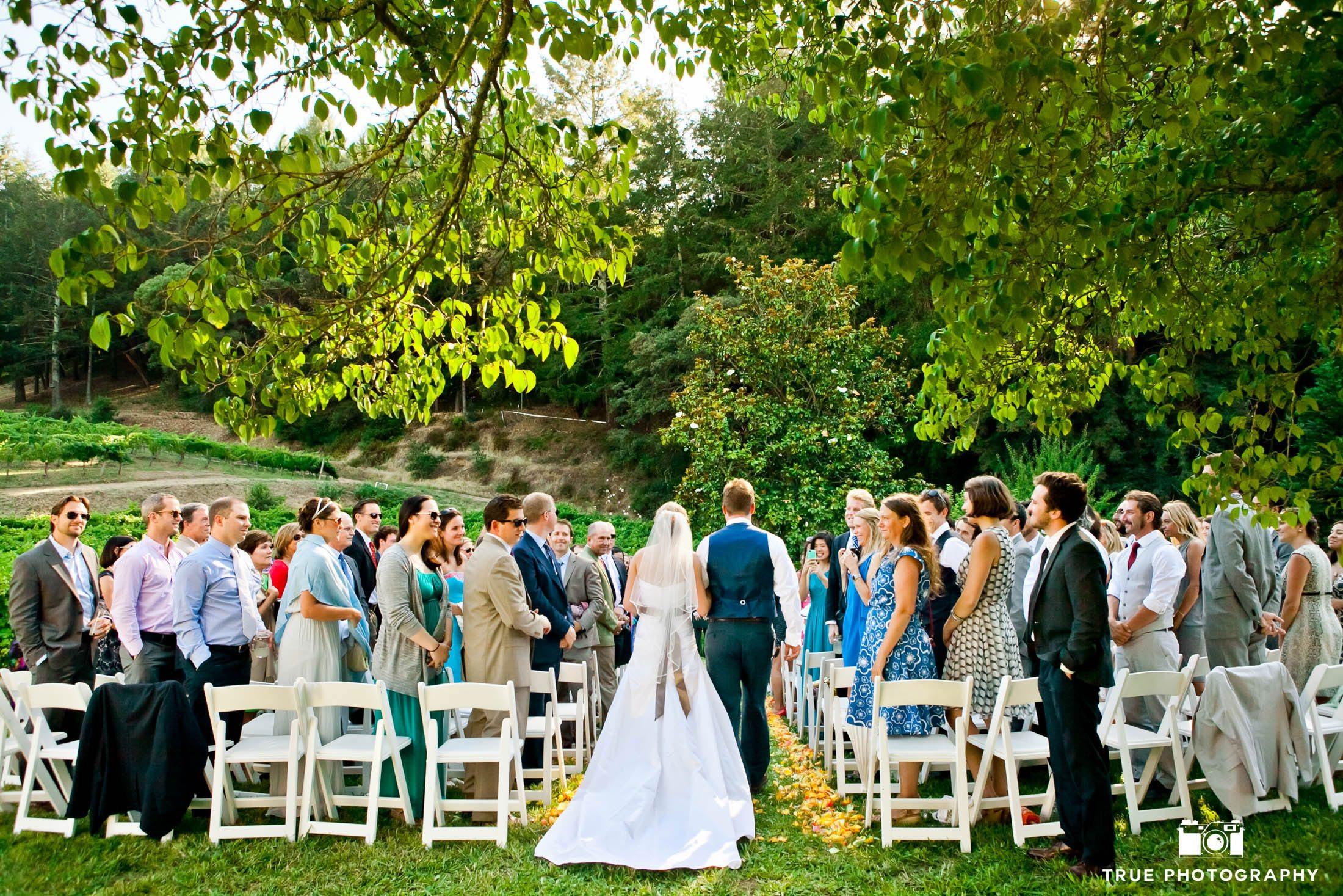Bride and Groom walk down aisle together at vineyard