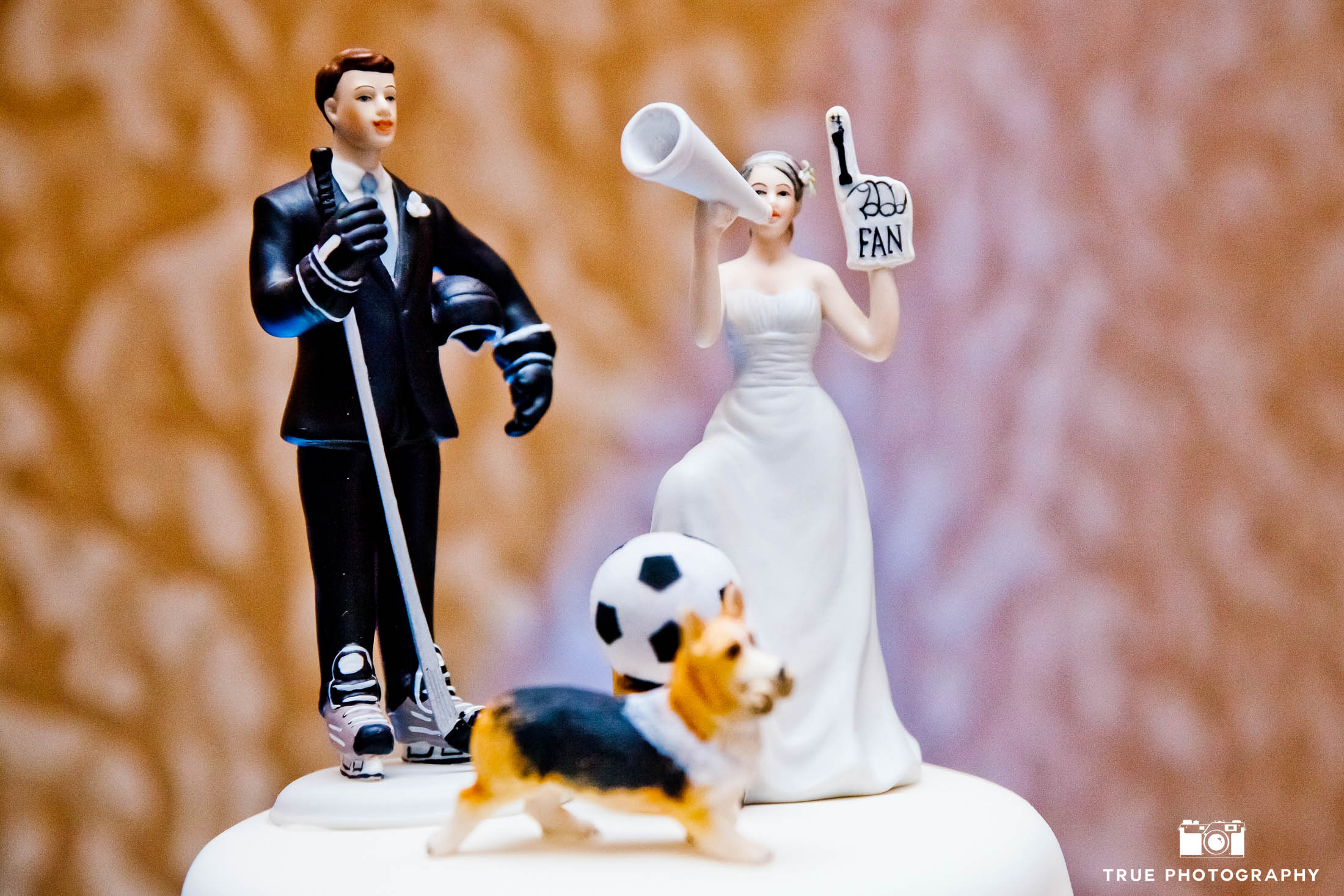Cute hockey-inspired cake topper with wedding couple
